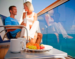 couple on cruise ship balcony with fruit plate